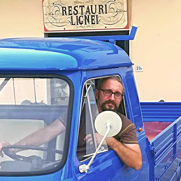 Michele Capperi on an old van restored in front of the artistic laboratory of San Casciano V.P. (Florence)