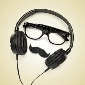 a pair of glasses, a mustache and a pair of headphones, and the word hipster on a beige background