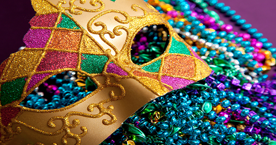 Gold mardi gras mask and beads