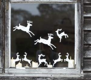 Simple white decals of Christmas reindeer on a window