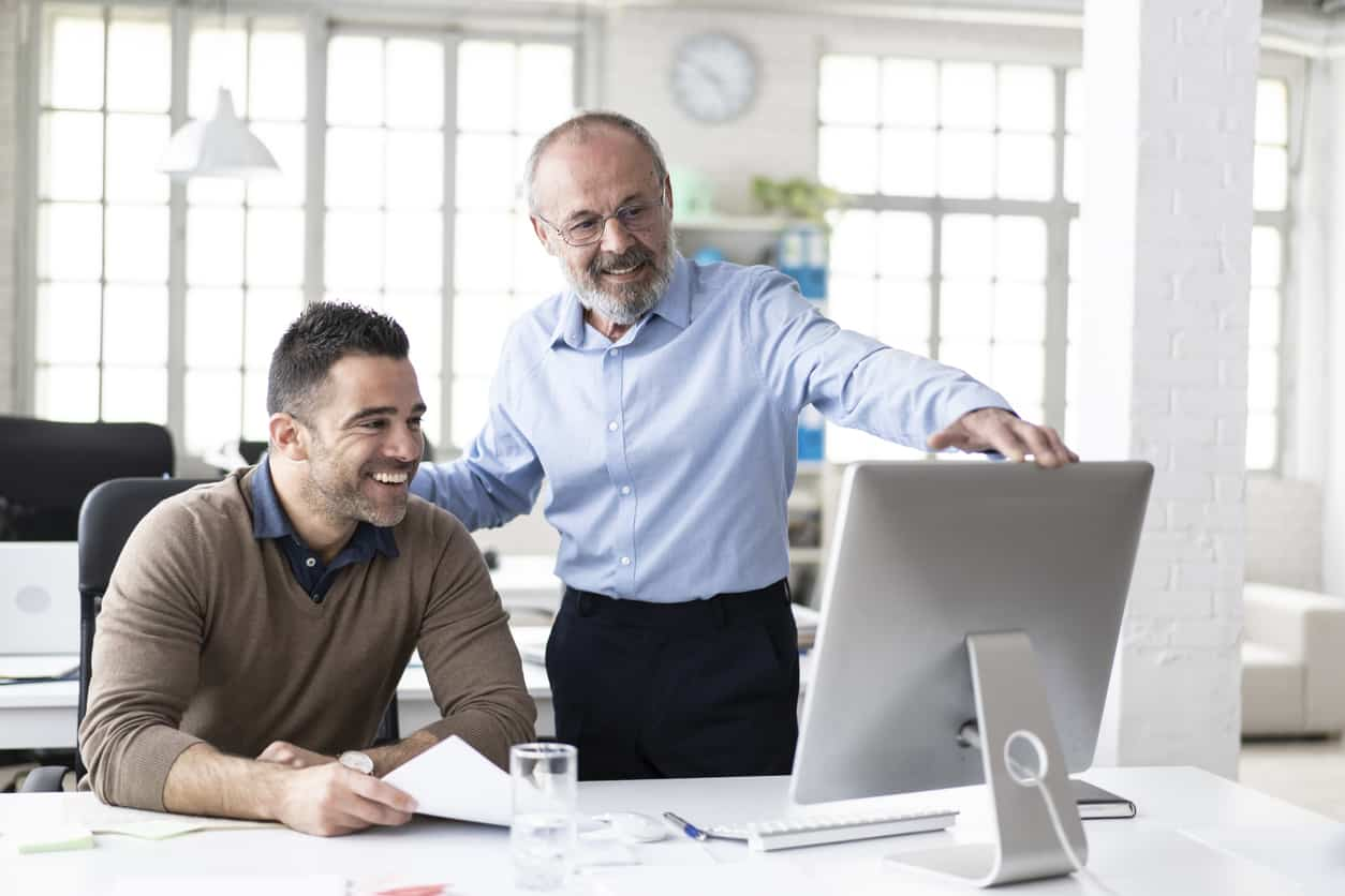 Senior manager explaining to coworker something on computer