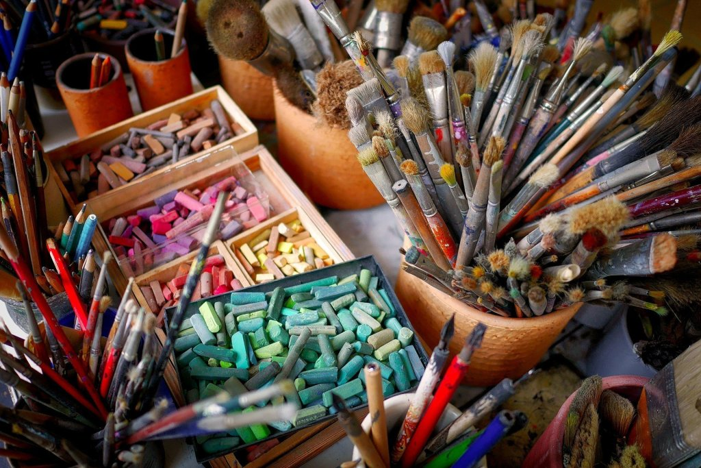 art supplies in jars and boxes on a desk - chalk, paintbrushes, pencils
