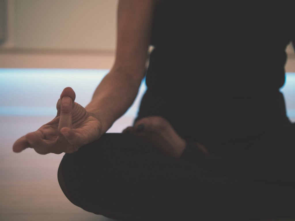 torso of woman sitting in lotus yoga pose with thumb and finger mudra