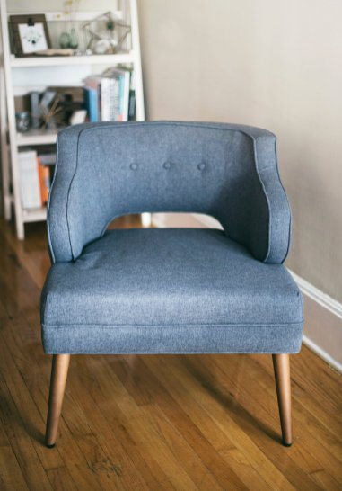 Scandinavian interior design with a grey blue mid-century modern chair on wood floor in front of white bookcase