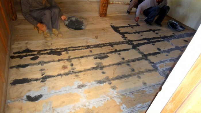 Applying on-site made floor board joint compound (wood glue, ash, resin)
