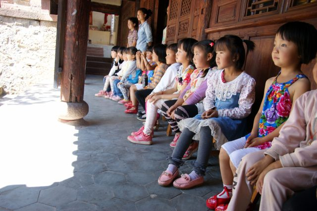 Children watching the temple dance performance - Shaxi Yunnan China