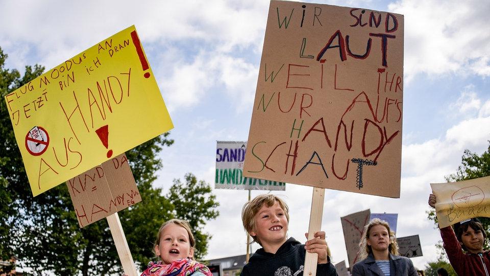 Bambini in piazza contro i genitori che stanno troppo al cellulare