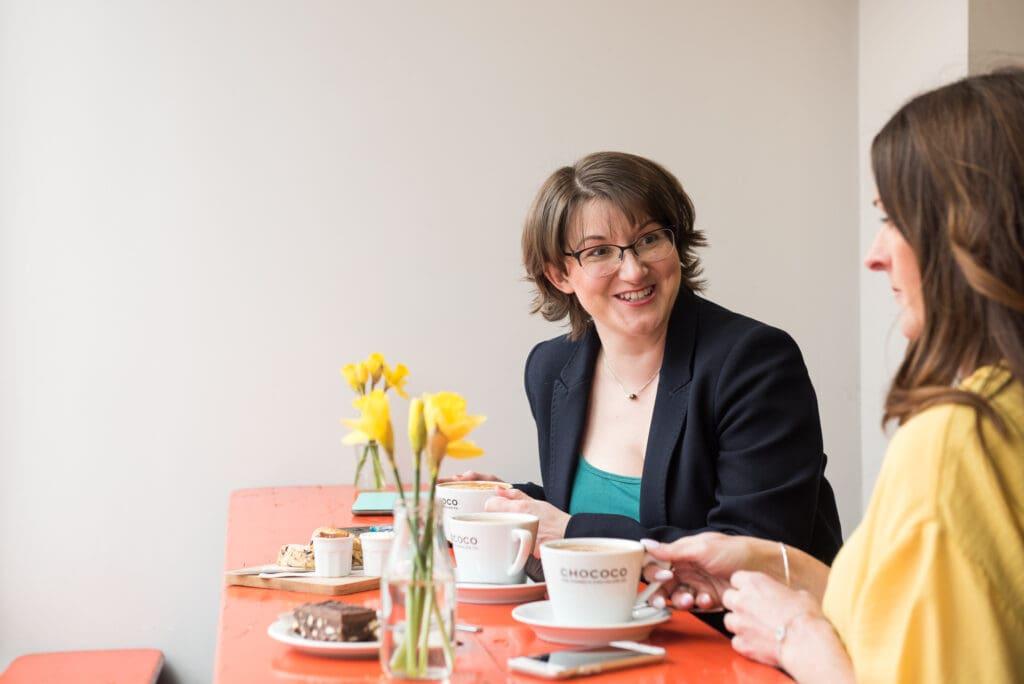 Elizabeth tomando un café con un colega