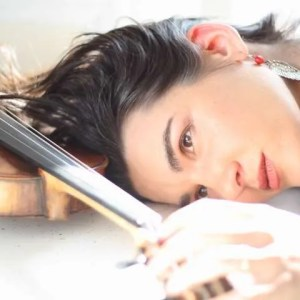 photo of Alicia Jo Rabins' head, lying down, turned to the side, holding a violin above