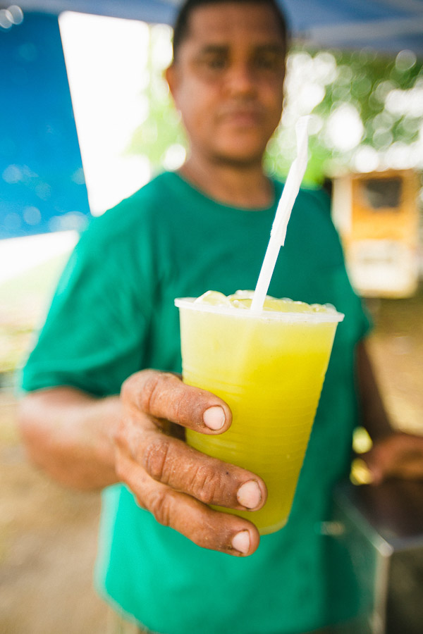 Travel Photography Tips for Non-Photographers: Image of a sugar cane juice maker handing me his final product after letting me photograph the process of creating the juice.