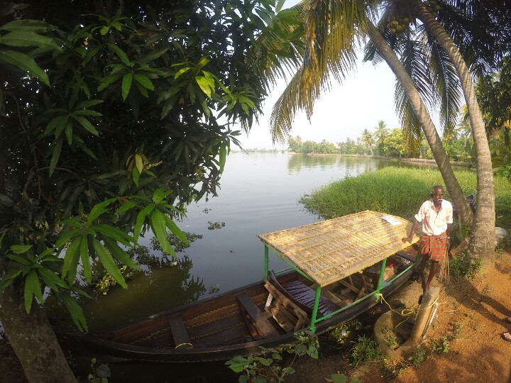 Indian man leaning on houseboat in Allepey Keralan backpwaters India