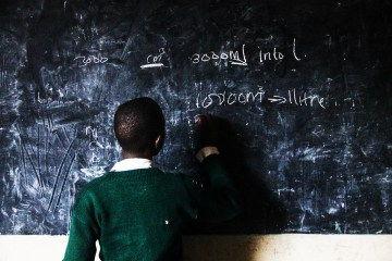 Kid writing on the blackboard during math lesson