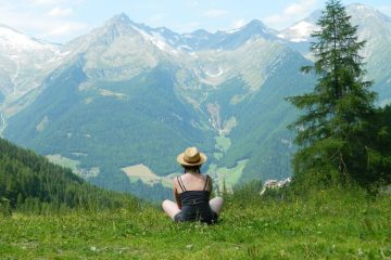 girl with hat on sat on grass admiring view of mountains italy