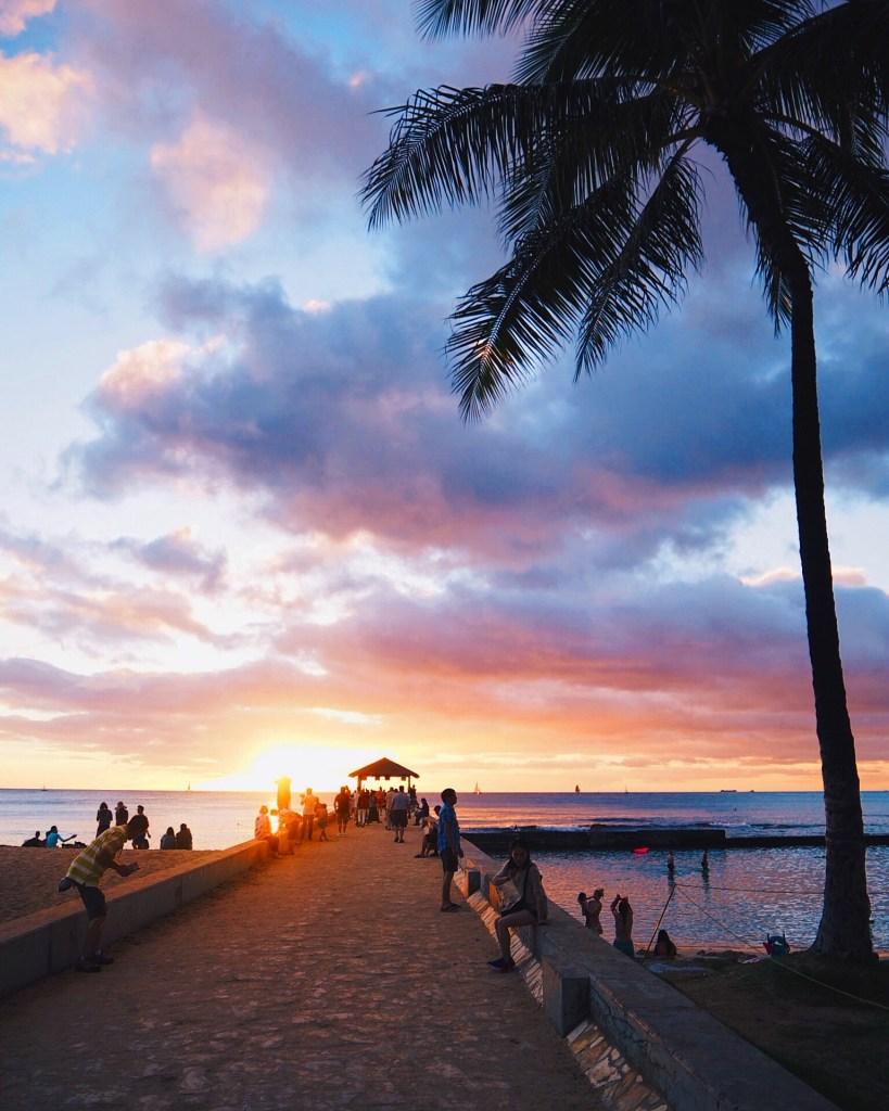 sunset view of sea, people walking down pier