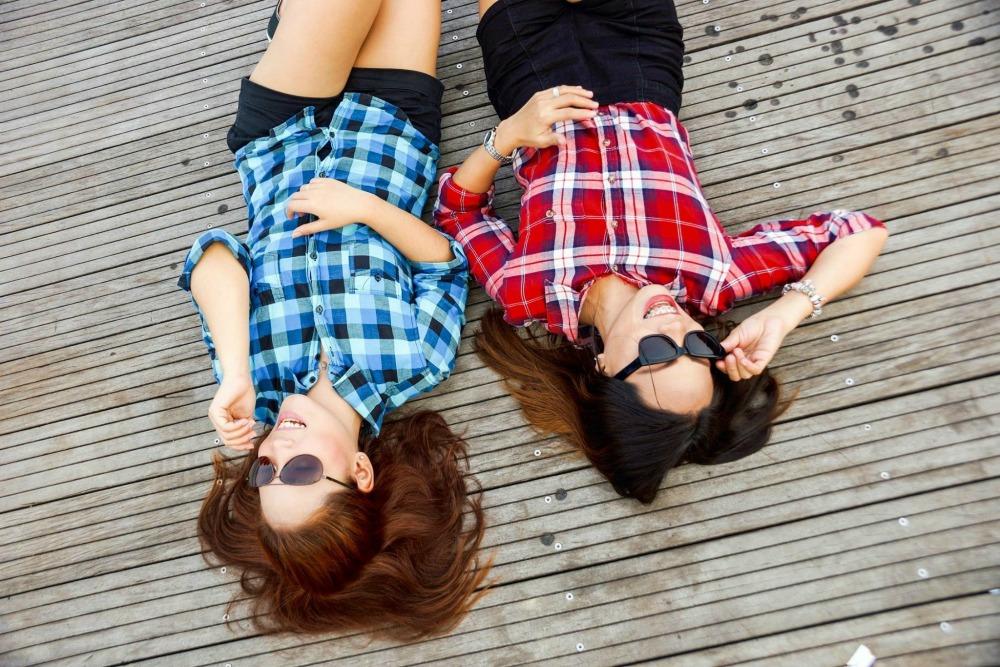 Making friends travelling - friends lying on floor on phones