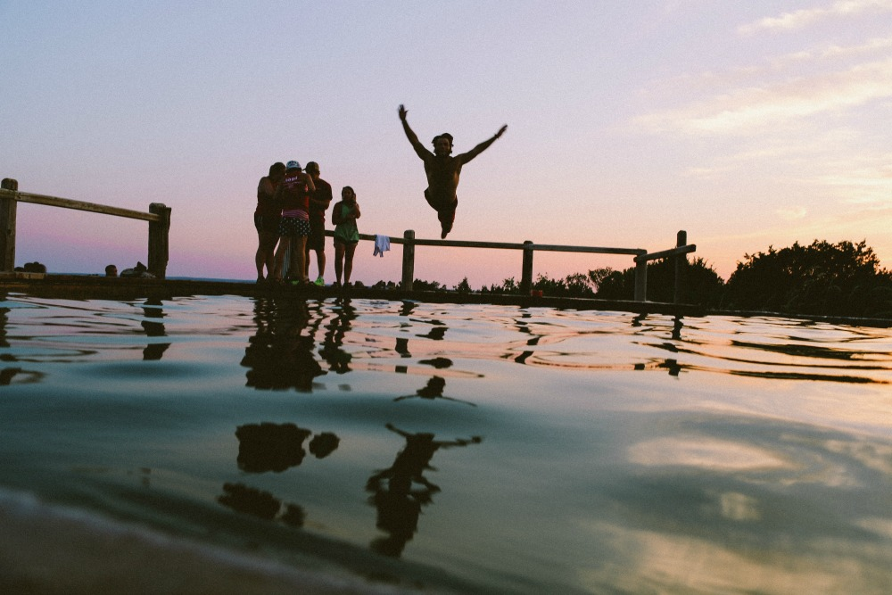 Making friends travelling - friends jumping into pool at sunset