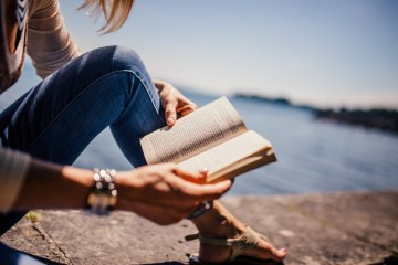 woman wearing jeans holding book on beach