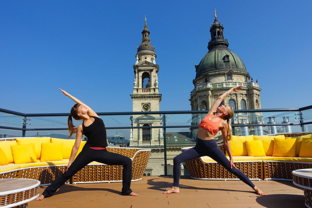 two girls doing yoga poses on rooftop in sun