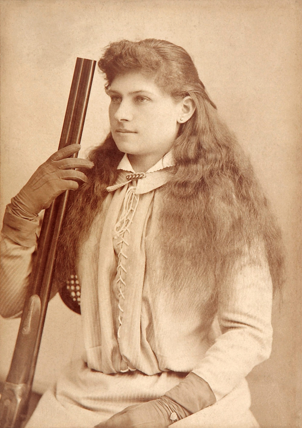 sepia image of annie oakley woman with gun