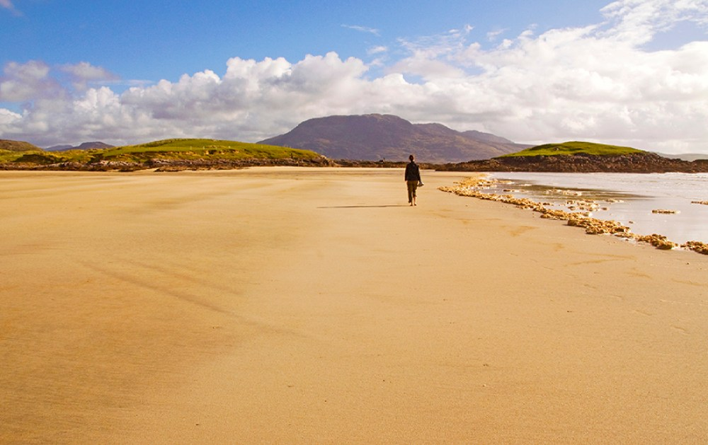 girl walking along a beach, with mountain in background, County Mayo, Ireland