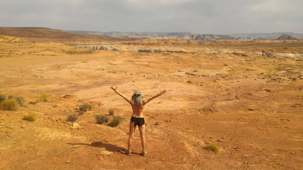 happy girl in bikini with hands up in desert