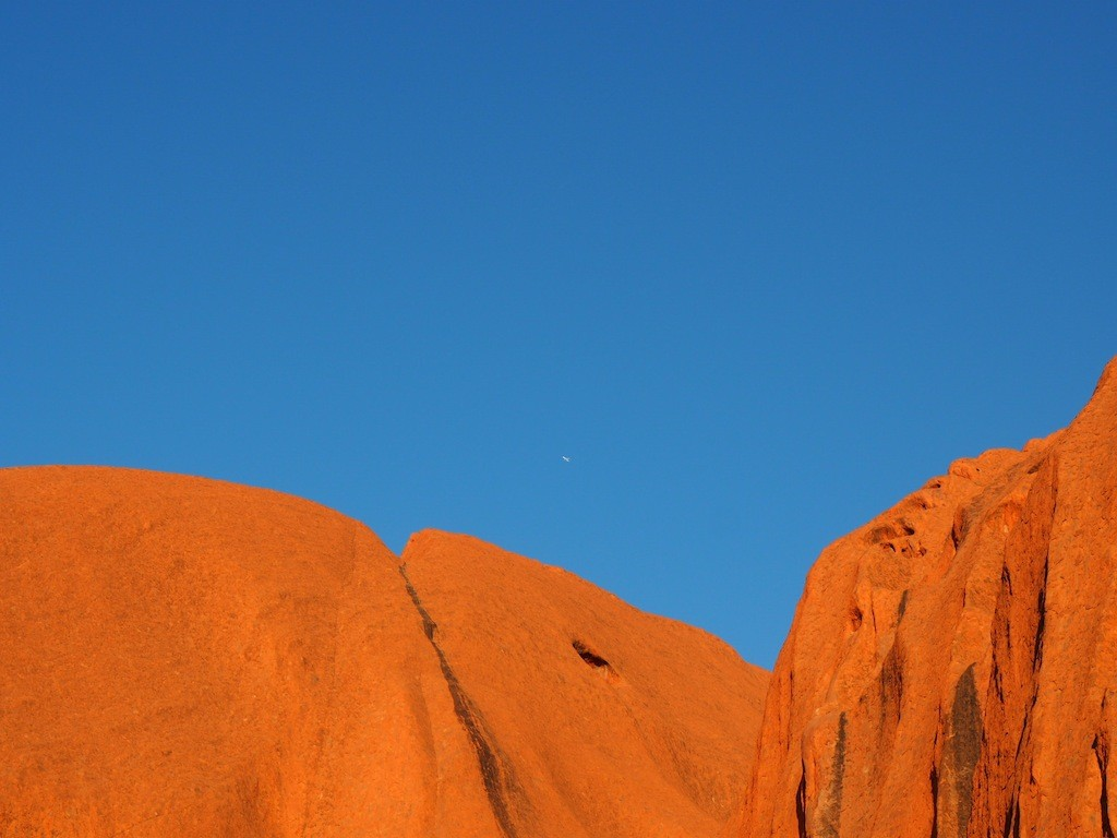 Look very closely and you'll see a plane leaving Ayers Rock airport behind Uluru