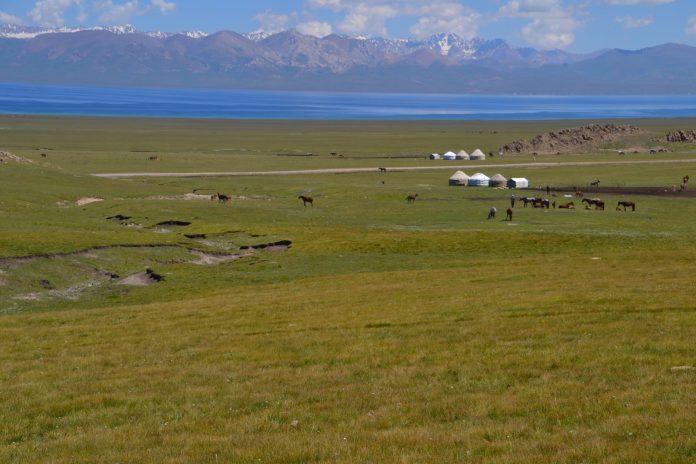 Het meer van Song Kul, omringd door groepjes yurts en hoge bergpieken