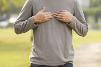man dealing with acid reflux at the park