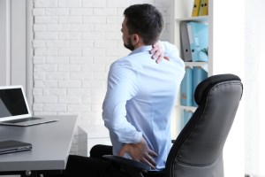 man sitting at desk working on his posture
