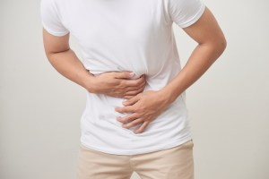 man suffering from stomach ache over white background