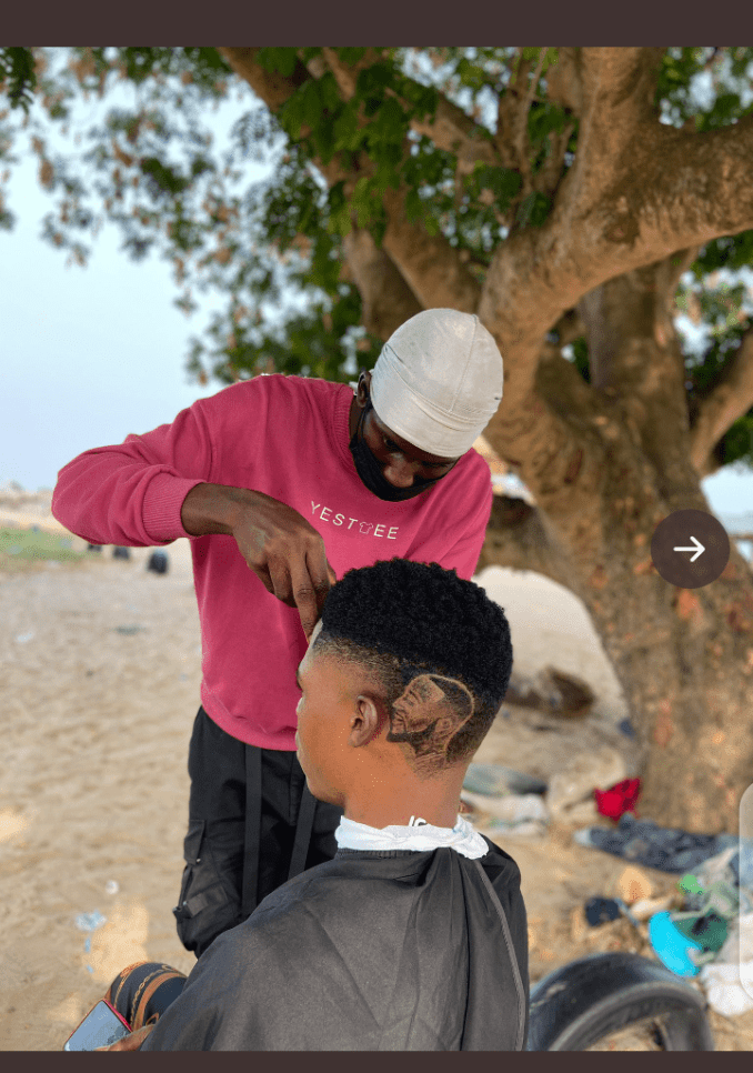 Davido acknowledges a young barber who carved a haircut on his customer with his face.