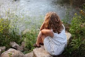 Stresset kvinde sidder i sommerkjole ved et vandløb