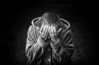 Ældre kvinder gemmer ansigtet i hænderne