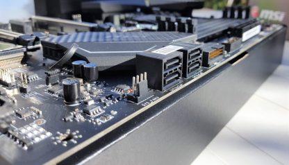De arriba a abajo: Puerto para bomba de agua, conector de ventilador de sistema nº 4, conector ATX de 24 pines, dos conectores USB 3,0 horizontal y vertical, 4 puertos SATA 3 y conector de ventilador de sistema nº 3.