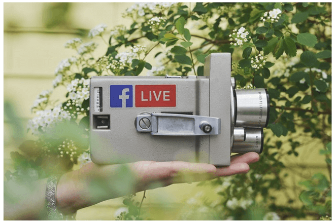 foto de una mano que sostiene una cámara de video con dos etiquetas relacionadas con facebook y la palabra LIVE