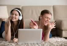 Jovenes mujeres con auriculares frente a una laptop