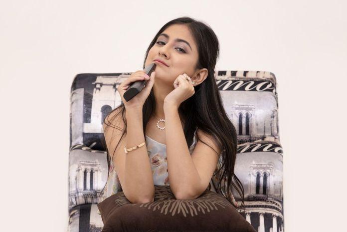 Joven mujer sentada en un sillón con un control remoto en la mano