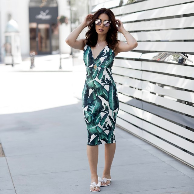 Fashion Blogger from Glam and Posh wearing a tropical summer dress and mirrored sunglasses  and white jelly sandals