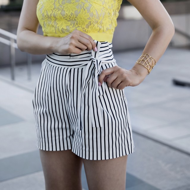 Fashion blogger wearing a yellow lace top with high waisted white shorts and lace up heels