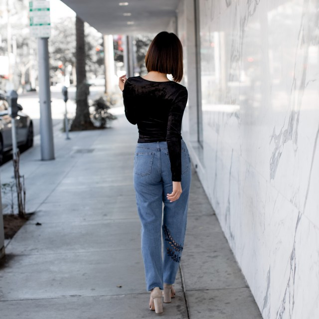 Fashion blogger Maryam Nia wearing high waisted jeans and velvet crop top for a date night outfit