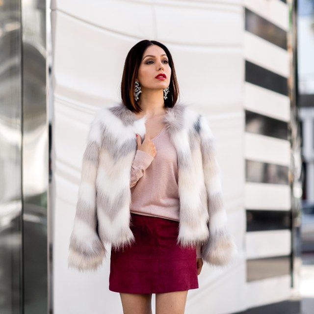 fashion blogger Maryam Nia wearing a statement faux fur coat by Nasty Gal and suede skirt