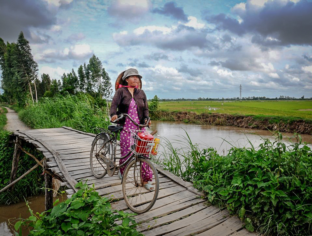 A local Vietnamese woman with her bike over a bridge in the Mekong Delta region