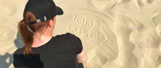 Katy Gossy Glanzlust Schrift im Sand geschrieben