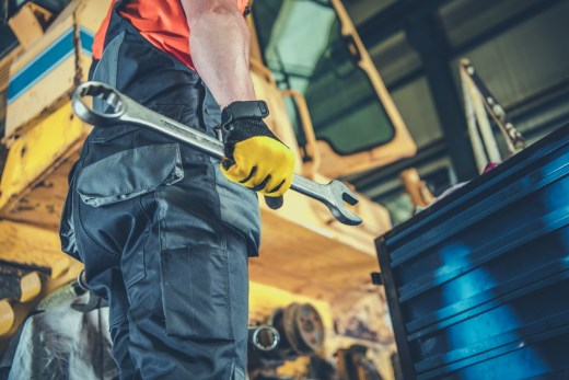 Maintenance on heavy machinery guide - Men with Large Iron Wrench Fixing Heavy Machinery. Industrial Job