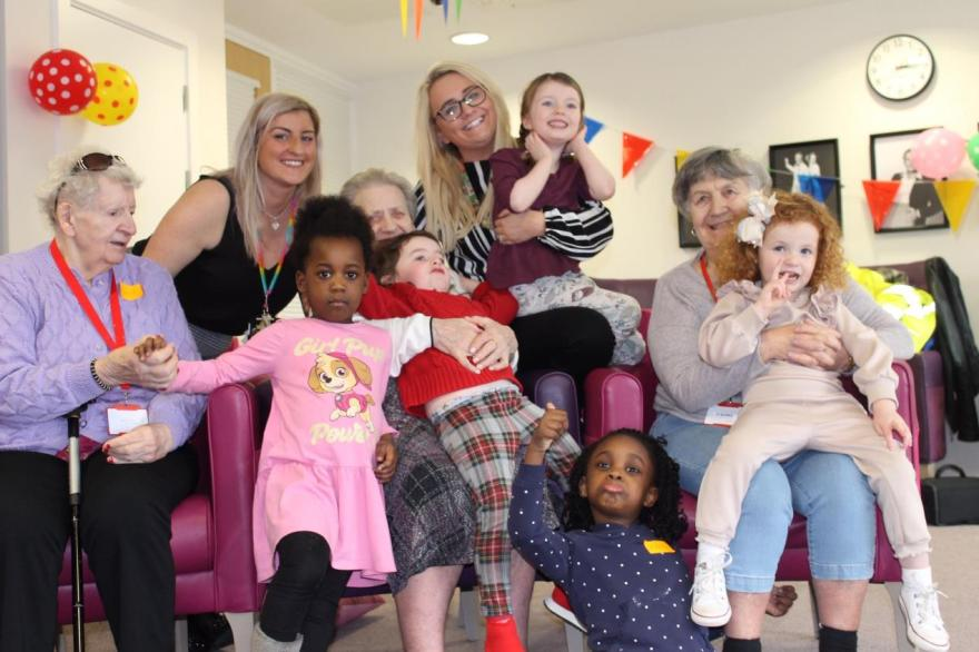 Nursery staff, Janine Al-Gailani (l) and Kathryn O'Neill, with the children and care home residents.