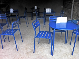 Photo: Blue chairs on concrete.