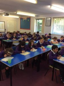 P4 Sitting in an old school style classroom.