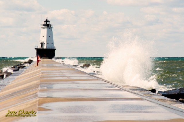 Ludington Light is swatted with small waves from both directions by Joe Clark www.glasslakesphotography.com