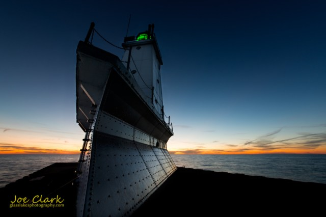 Sun sets behind the Ludington Lighthouse. By Joe Clark www.glasslakesphotography.com