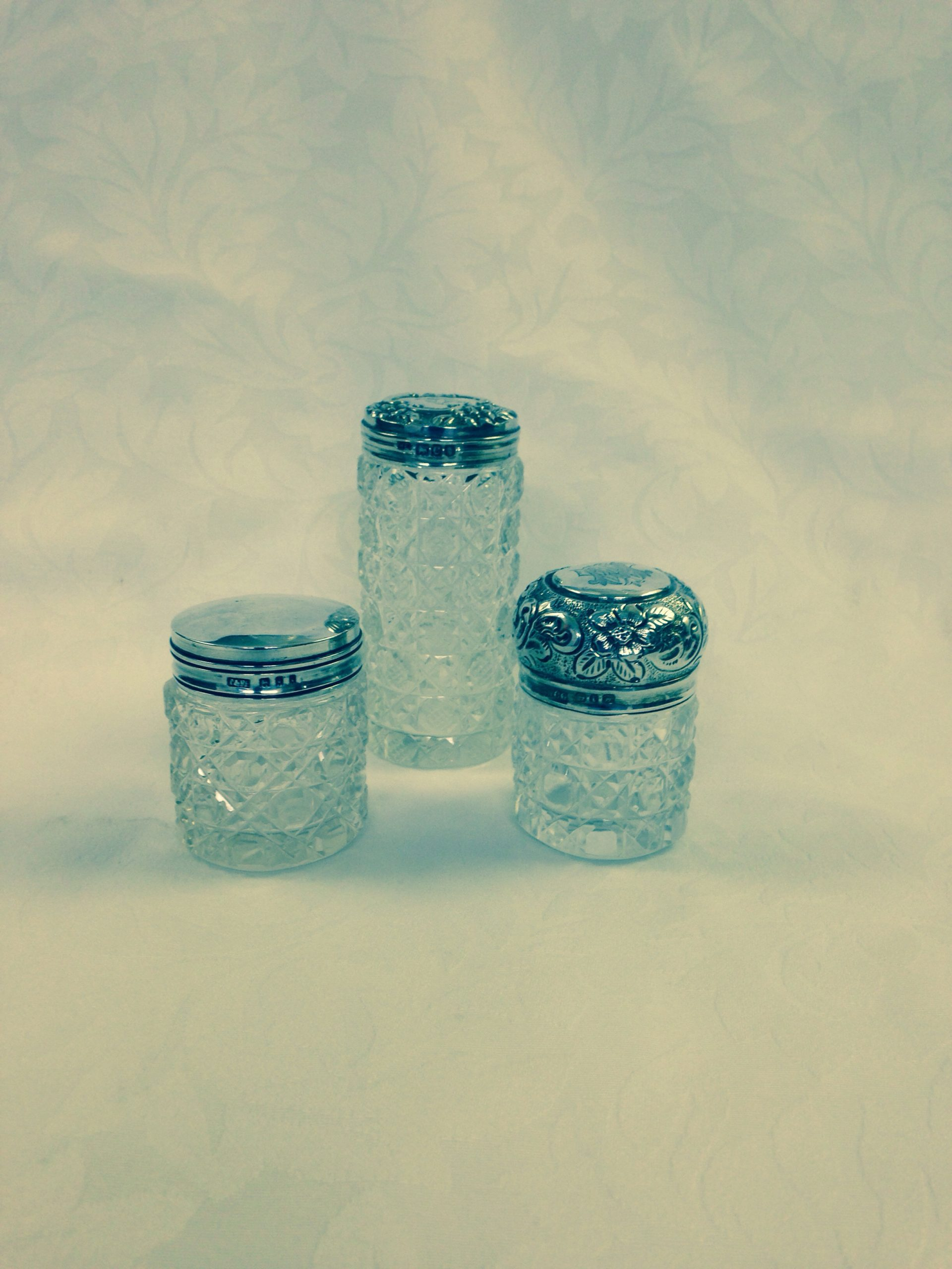 Cut glass jars supplied ans fitted to silver lids All chips repaired